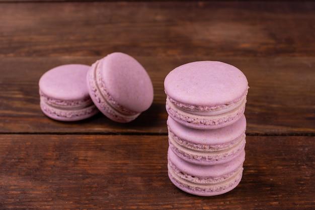 木製の背景に美しいピンクのおいしいマカロン
