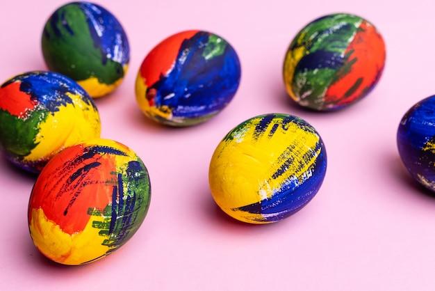 Разноцветные пасхальные яйца, краски и кисти на столе. подготовка к празднику