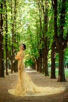 自然を背景に黄色のドレスの美しい少女