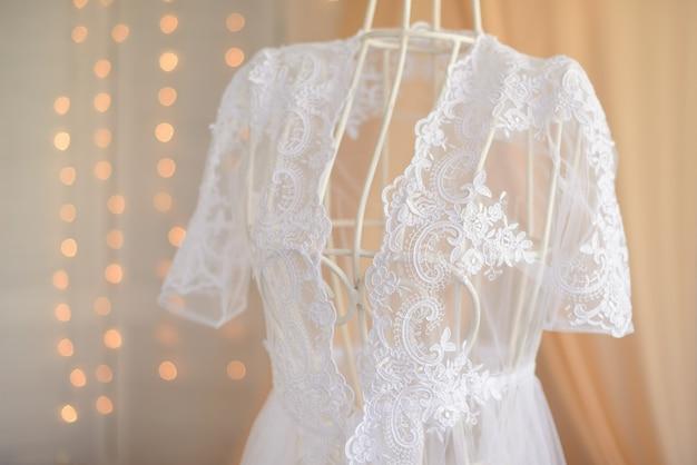 ダミーからぶら下がっている白いウェディングドレス