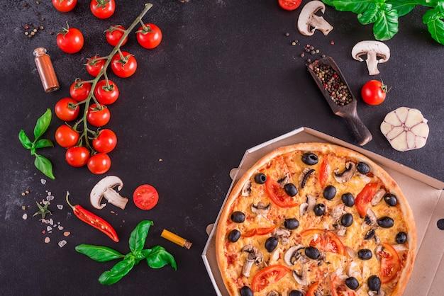 暗い背景に対しておいしい新鮮な熱いピザ