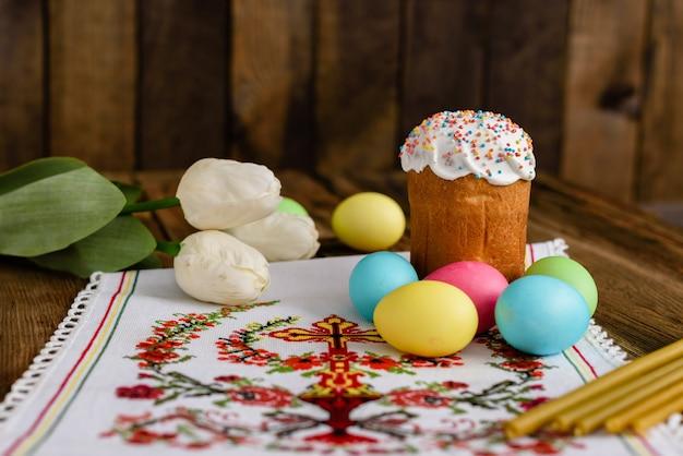 Пасхальный кулич и красочные яйца на деревянном столе.
