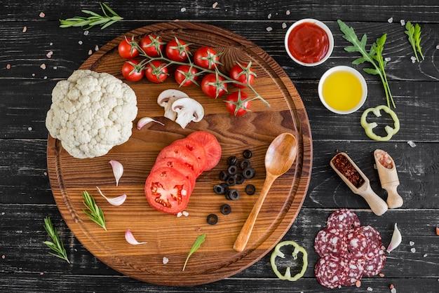 ピザの製造に生地と野菜の準備。木製の背景上のピザの生産のための原料