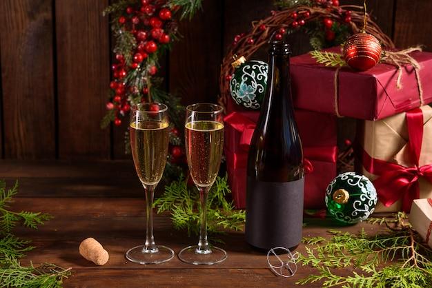 グラスとシャンパンのワインのボトルとクリスマスの休日テーブル