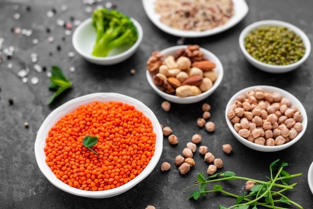 コピースペースを持つコンクリートの背景に健康的なビーガンフード。ナッツ、豆、野菜、種子