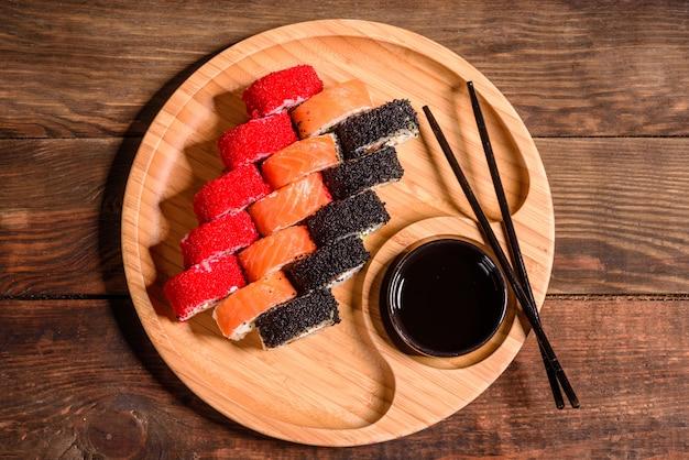 さまざまな種類の寿司が暗闇で出されました。サーモン、アボカド、キュウリを巻きます。寿司メニュー。日本食。