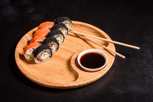 Различные виды суши подаются. ролл с лососем, авокадо, огурцом. суши-меню. японская еда.
