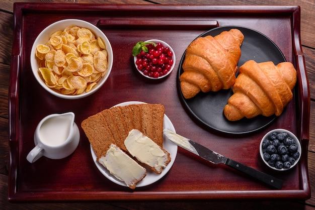 焼きたてのクロワッサンと美しい木製のテーブルに熟した果実のおいしい朝食