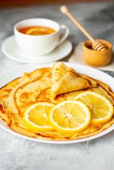 食べ物、デザート、ペストリー、パンケーキ、パイ。バナナとコンクリートの背景に蜂蜜のおいしい美しいパンケーキ