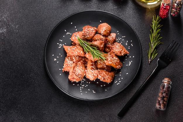 Куриное филе в кунжуте, соус терияки на черной каменной плите. азиатская кухня