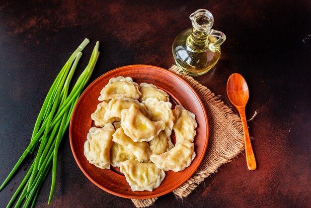 Вареные пельмени с начинкой из масла и зеленого лука на темном столе. может использоваться как фон