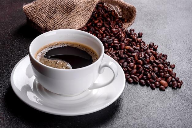 一日の元気なスタートを切るためのフレッシュな香りのモーニングコーヒー。暗いテーブルの上のコーヒーと美しいコーヒーカップ