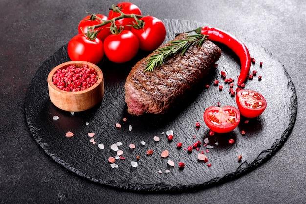 Рибай стейк с картофелем, луком и помидорами черри. сочный стейк с ароматным маслом