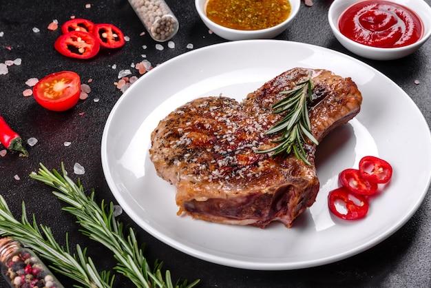 野菜とスパイスで骨に新鮮なおいしいジューシーステーキ暗いテーブルに豚肉ジューシーステーキグリル