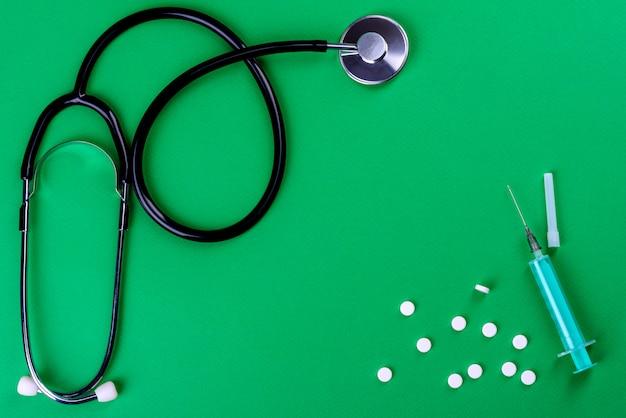 Вид сверху предметов медицинского назначения: стетоскоп, шприц и таблетки