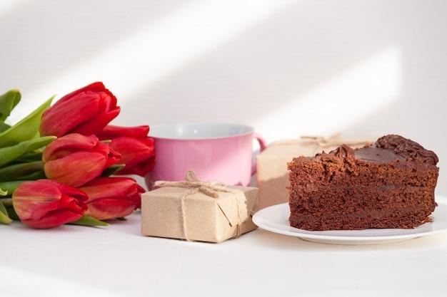 朝。チューリップ、プレゼント、ケーキ、母のためのカップ、妻、娘、愛を込めて女の子。お誕生日おめでとうございます、