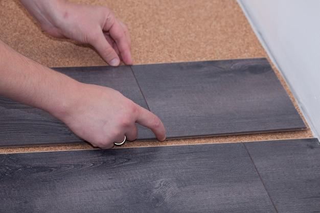 男は家の中で積層のフロアーリングを敷設