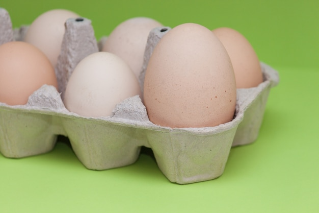 カートンの卵、薄緑色の背景に他の小さな卵の中で最大。コンセプトメイン、リーダー、重要。
