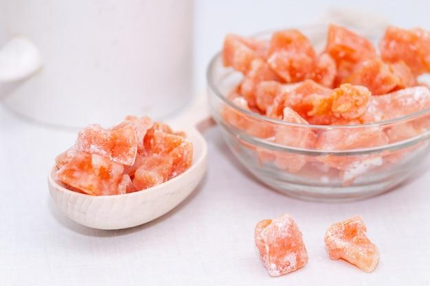白い背景の上の木のスプーンでカボチャから自家製砂糖漬けの果物。健康的なおやつ。