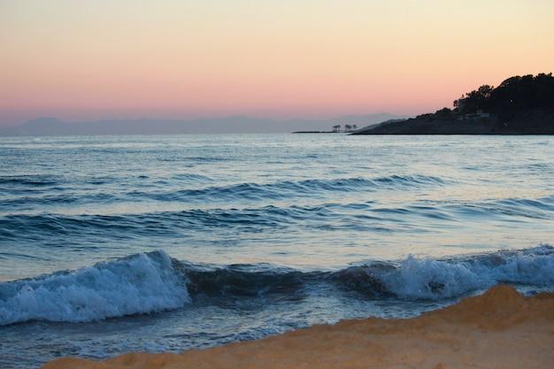熱帯のビーチの夕日の風景です。波、山、ヤシの木。