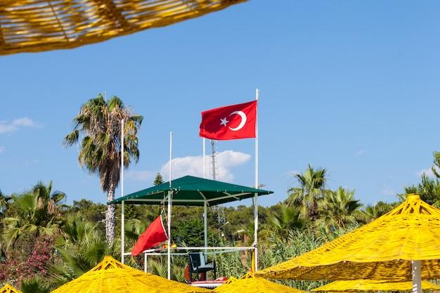 ビーチでトルコの国旗。黄色いビーチパラソル。