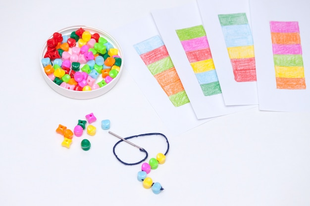 プラスチック製の多色ビーズ。子供たちの開発の概念のための自家製ゲーム。