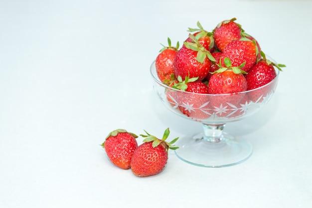 白い背景の上のガラスのボウルで、新鮮なイチゴ