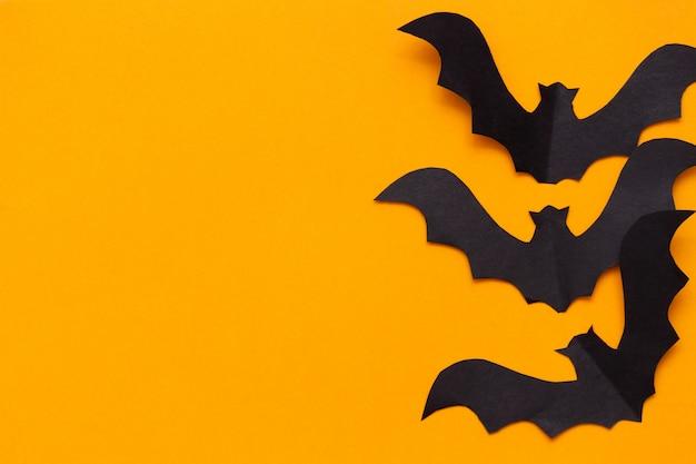 オレンジ色の背景に黒い紙から切り取った黒いコウモリの姿。フラット横たわっていた、コピースペース、トップビュー。