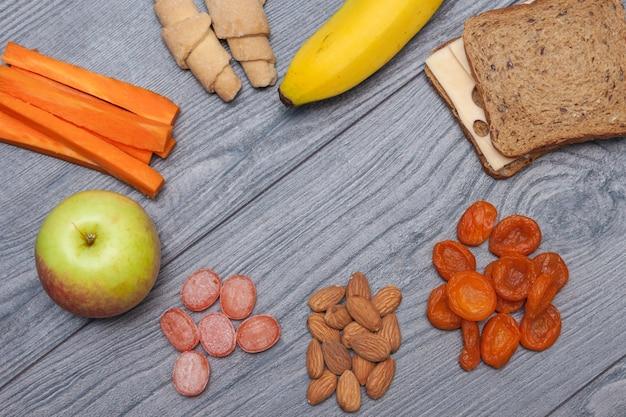 チーズ、リンゴ、バナナ、アーモンド、ドライフルーツ、水、天然キャンディー、ニンジン、ビスケットサンドイッチ、サンドイッチ、コピースペース、平干し、トップビューで健康的な学校給食。