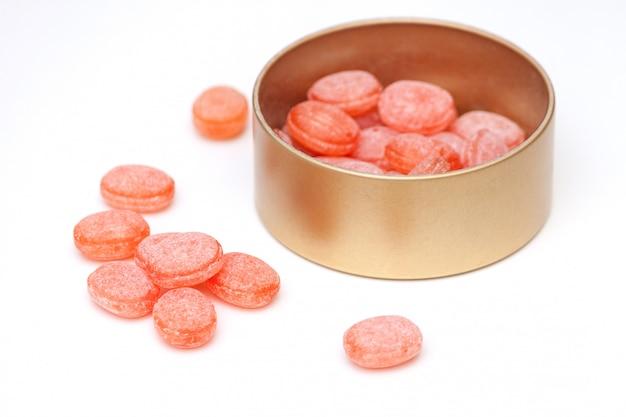 Оранжевые конфеты в жестяной банке на белом