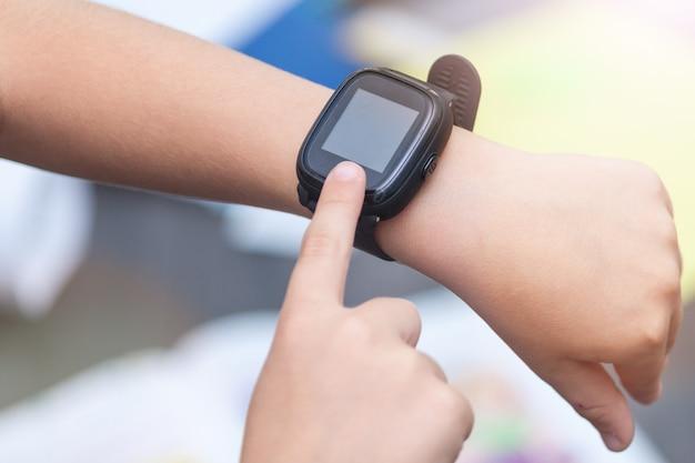 スマートな時計で子供の手のクローズアップ。電子時計に触れる。