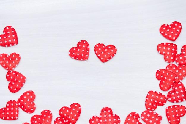 バレンタインデーの背景。白い木製の背景に赤いハート。バレンタインの日、愛、結婚式のコンセプト。フラット横たわっていた、トップビュー。