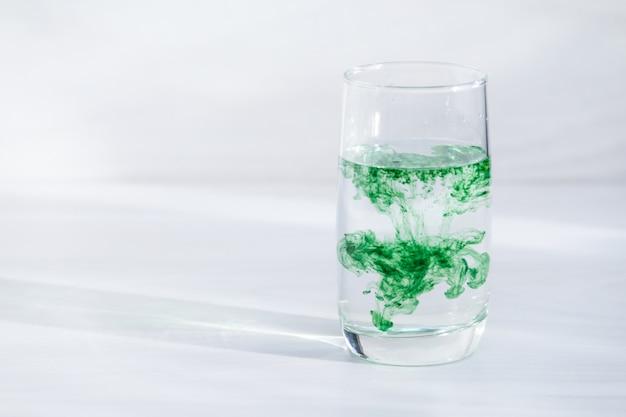 水のガラスに含まれるクロロフィル。コピースペース、日光。