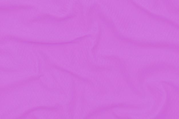 Абстрактная неоновая фиолетовая предпосылка текстуры ткани. ткань мягкая волна. закройте, задрапированный.