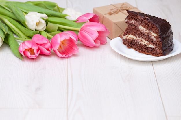 ピンクのチューリップ、チョコレートケーキの花束。プレゼントボックス。スペースをコピーして、クローズアップ。母の日の概念。
