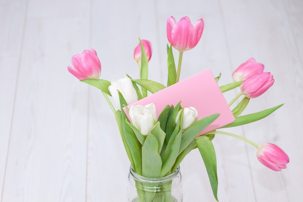 Розовый букет тюльпанов в стеклянной вазе на белой деревянной поверхности с карточкой. поверхность весны, праздник, концепция дня рождения.