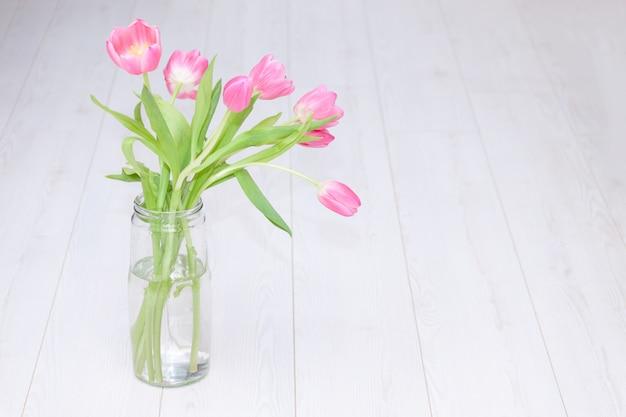 Розовый букет тюльпанов в стеклянной вазе на белой деревянной предпосылке. копировать пространство весенний фон, праздник, день рождения концепции.