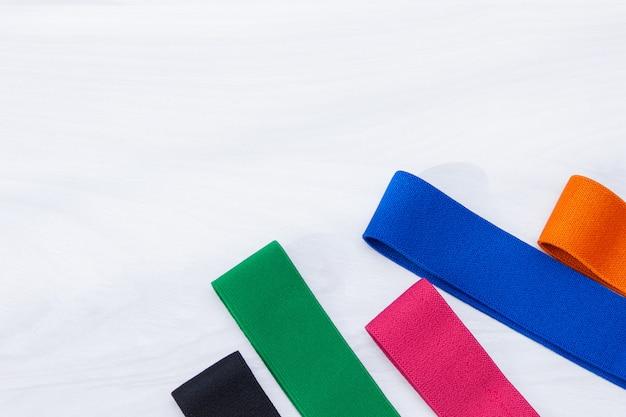 白い木製の背景にフィットネスのためのマルチカラーの弾性ゴムバンドのセット。フィットネストレンド、スポーツコンセプト。