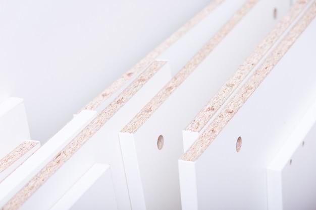 白い木製パネルまたはボードクリップボードは、家具製造用の部品をカットしました。
