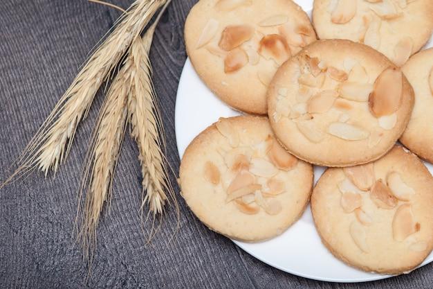 アーモンドと小麦の木製の背景上の皿においしいクッキービスケット