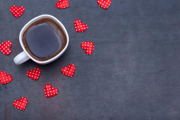 Чашка черного кофе и сердца на черном фоне.