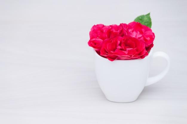 Цветет красные розы в чашке на деревянной предпосылке. плоская планировка, вид сверху, цветочный фон.