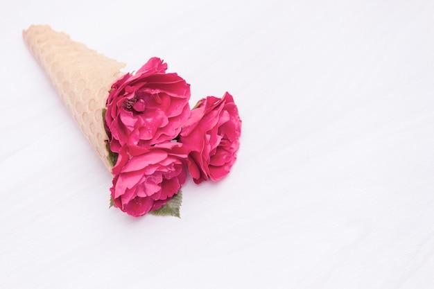 Цветет красные розы в вафельном конусе на белой деревянной предпосылке. плоская планировка, вид сверху, цветочный фон, тонированное.