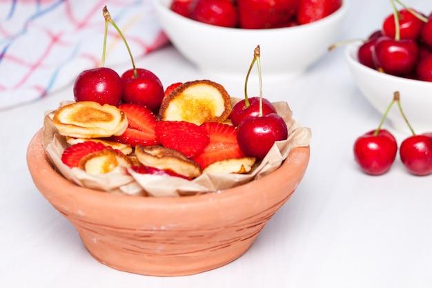 ストロベリーとチェリーの白い木製の背景にミニの小さなパンケーキ。トレンディな食品のコンセプトです。