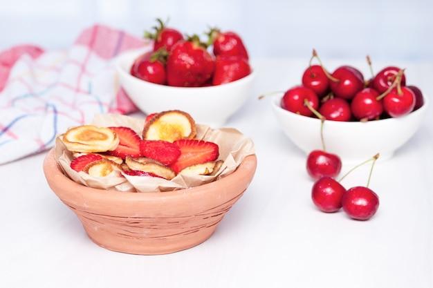 イチゴとチェリーの白い木製の背景にミニの小さなパンケーキ。トレンディな食品のコンセプトです。