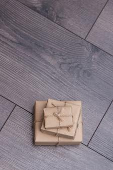 木製の背景に袋ロープでペーパークラフトに包まれたプレゼント。