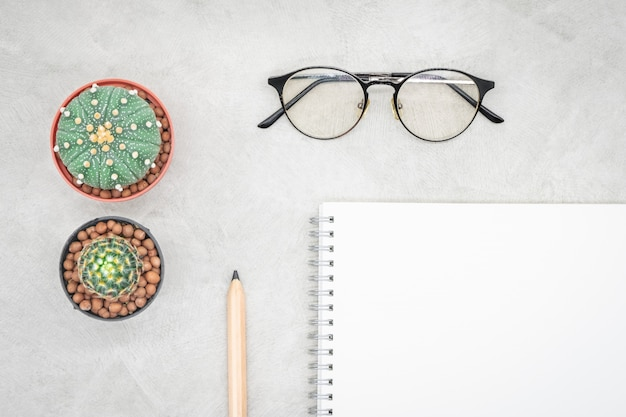 サボテン、ノート、眼鏡、オフィステーブルの上の鉛筆