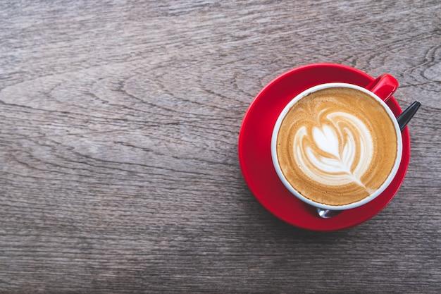 木製テーブルの上のラテアートコーヒーカップ、フラットレイアウト