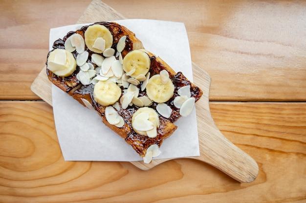 木製のテーブルにチョコレートバナナイチゴとアーモンドのフレンチトースト