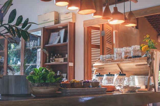 Разнообразие зерна и семян растений с салатными растениями и заправкой здоровой пищи в деревянной миске на деревянный стол